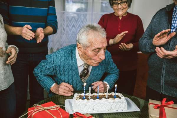 Grandfather celebrates birthday surrounded with presents and his loved ones