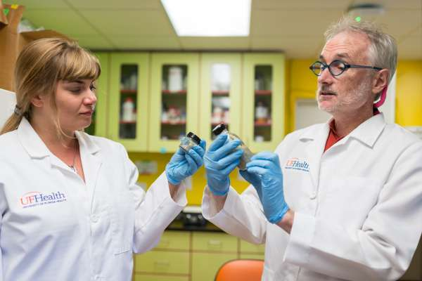 Dr. Devrah Arndt and Dr. Chris Vulpe hold thick and thin silver nanowire suspensions.
