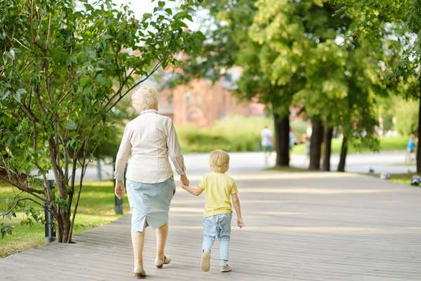 Beautiful granny and her little grandchild walking together in park.