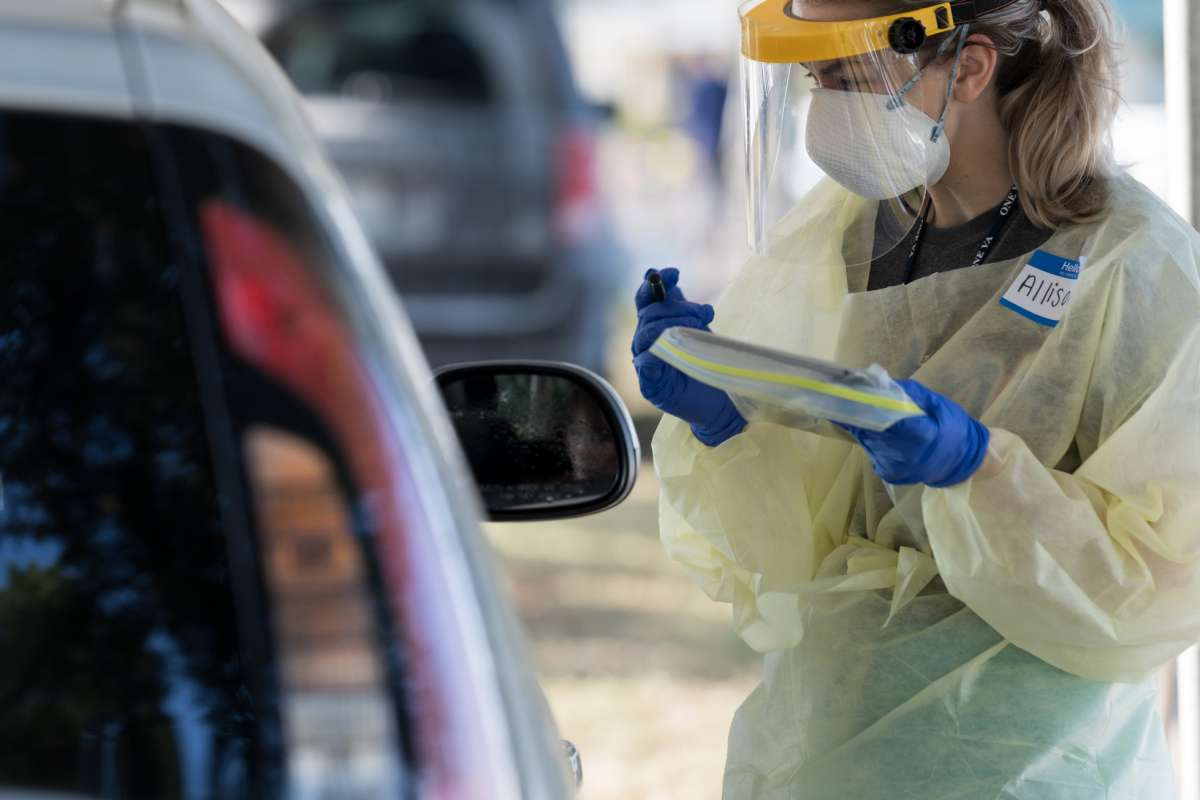 front line health care worker conducts a COVID-19 assessment near a patient's car