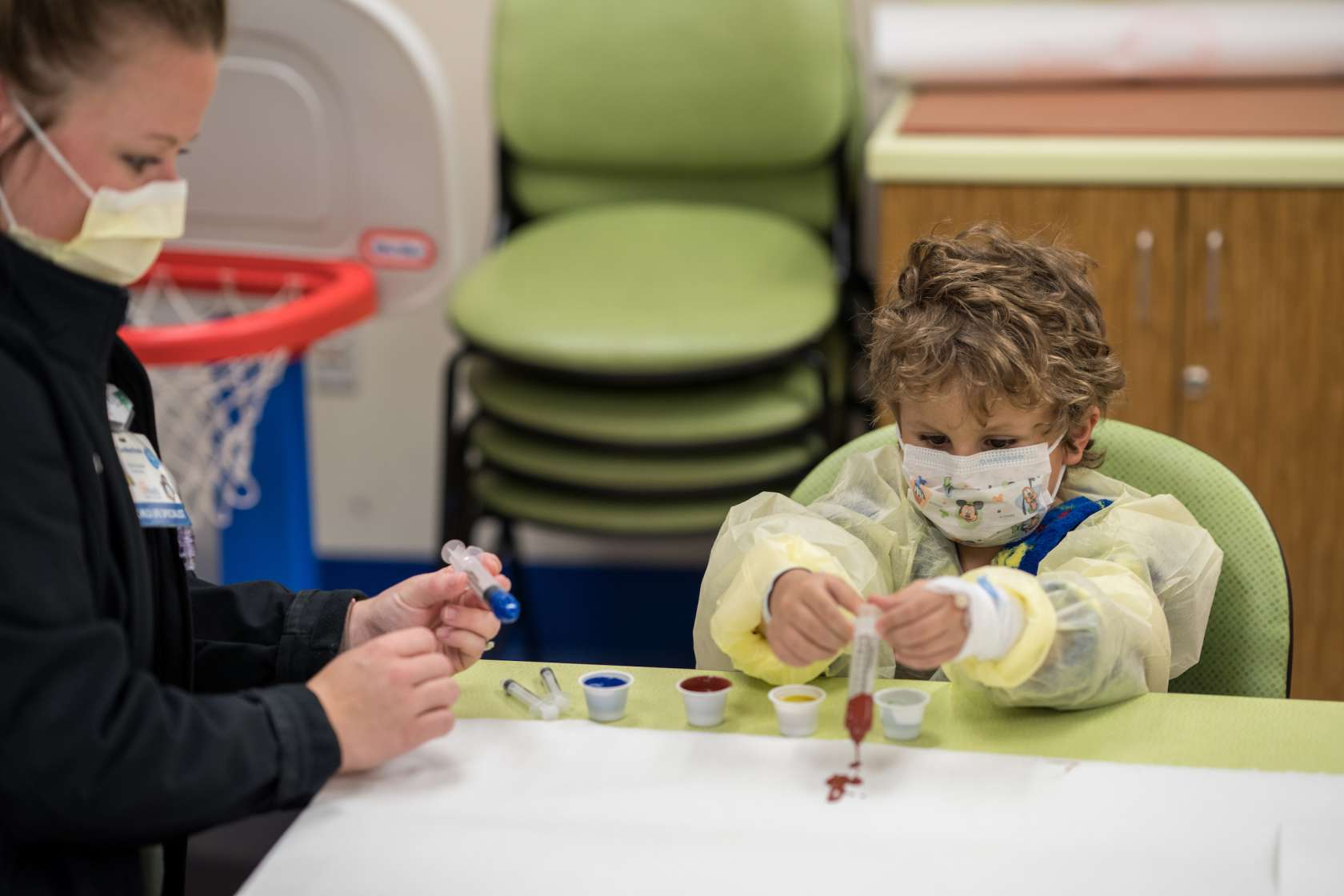 Caroline Erwin, Child Life Specialist, spends some time with Benjamin, five years old, creating art by syringe painting and also playing Foosball.